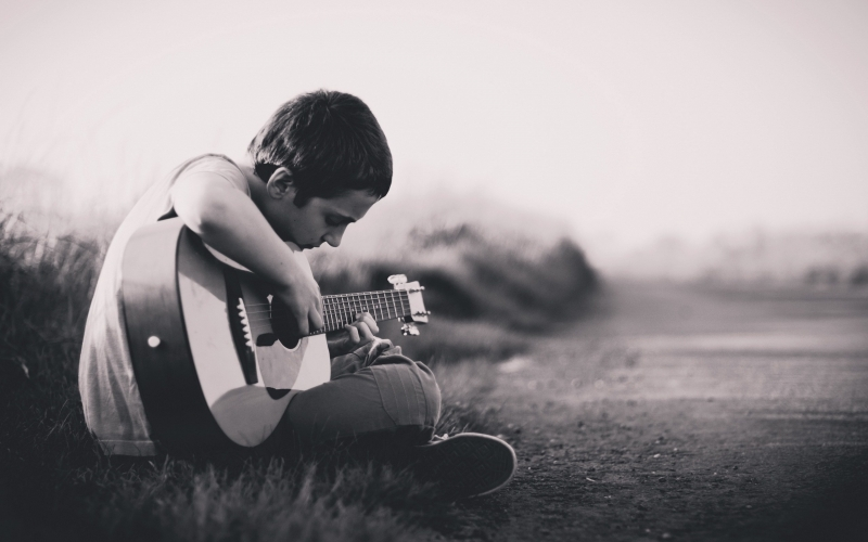 enfant qui joue de la guitare assis dans l'herbe